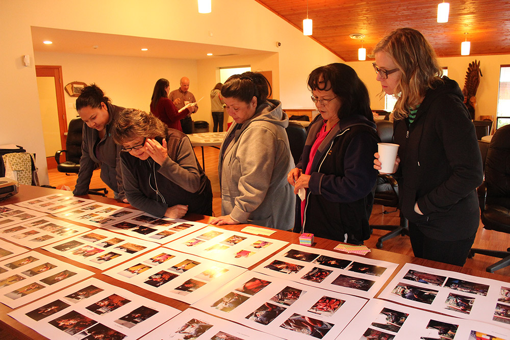 Five people are gathered around a long rectangular table, leaning forwards and looking at many pages of photographs laid out on the table in front of them.