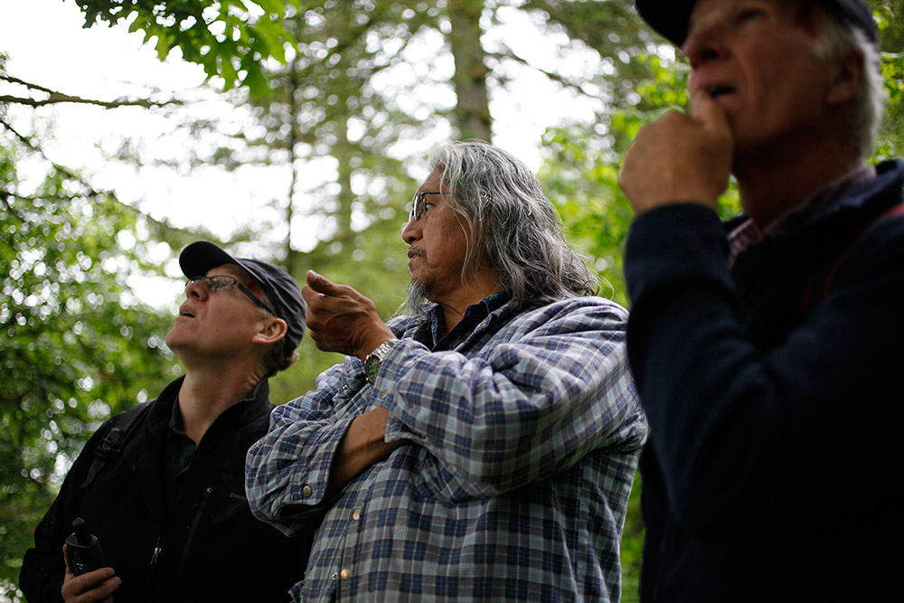 Three men standing and talking in a forested area.
