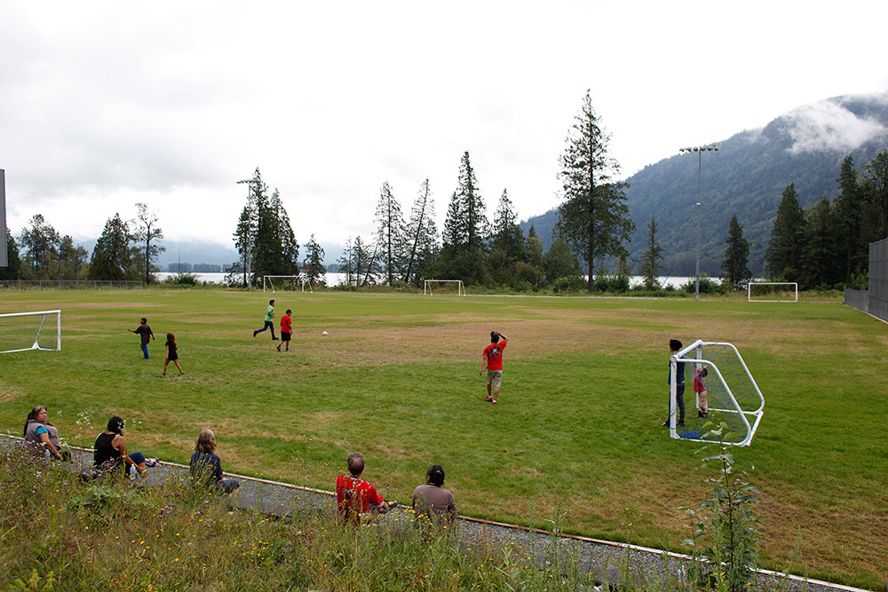 A game of soccer is being played on an outdoor grass field, with trees and mountains in the background. In the foreground, several spectators are leaning against a fence watching the game.