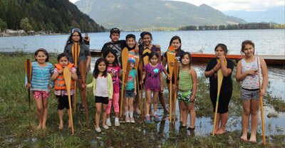 Fourteen young children standing near the shore of a river, smiling, and holding onto canoe paddles that are positioned in front of them vertically. A canoe is behind them. In the background is the river, and green mountains in the distance.