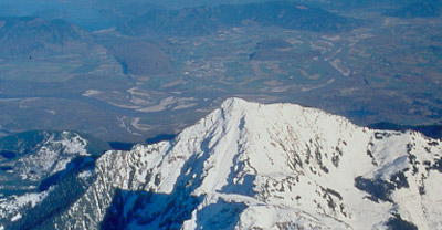 Aerial view of a snow-capped mountain with a green mountainous landscape in the background.
