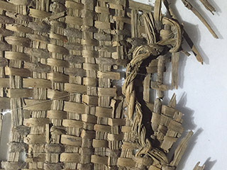 A close up view of the rim, body, and handle of a fragmented basket woven from bark strips.