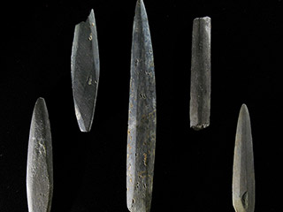 Five pieces of narrow stone are shaped into points. One has the point broken and another does not taper.