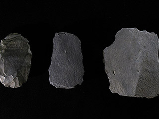 Three pieces of dark grey stone with sharp edges on a black background.