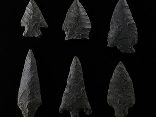 Six arrowheads of different sizes made of dark grey stone on a black background.