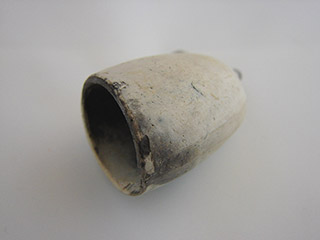 Smooth surfaced white hollowed cup shaped like a pipe bowl.