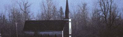 A side view of a small church in a field. In the background is a forest and a snow-covered mountain.