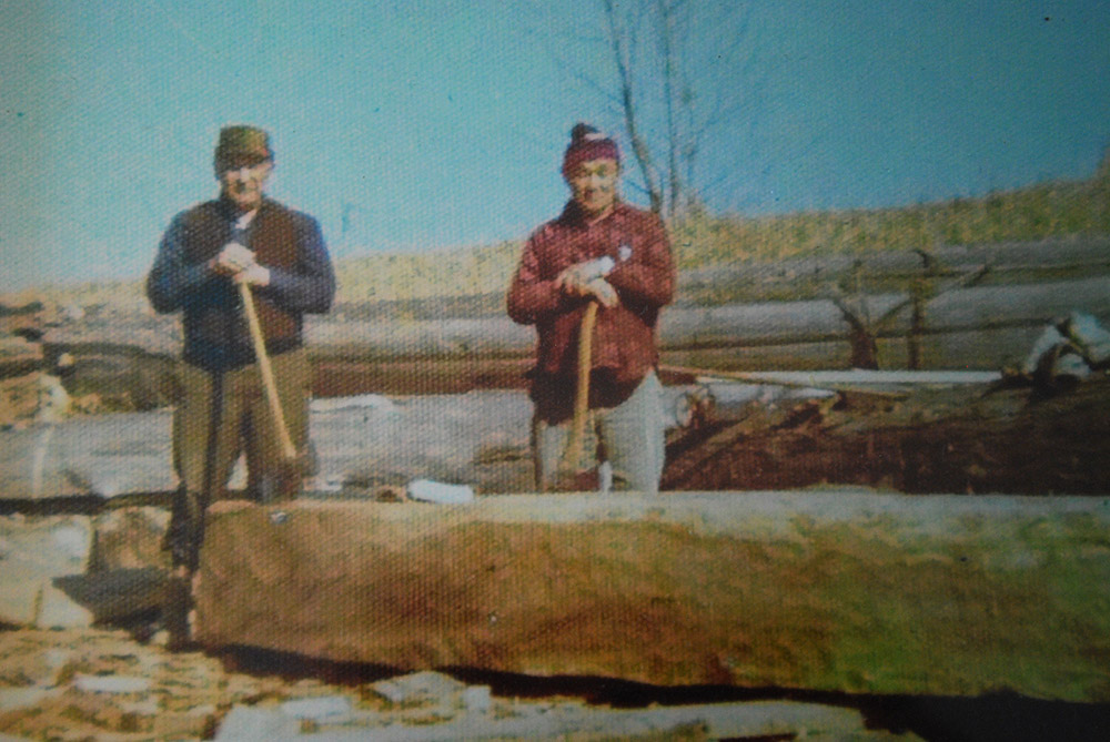 Two men stand behind a log. Both men are holding axes that are resting on the log.
