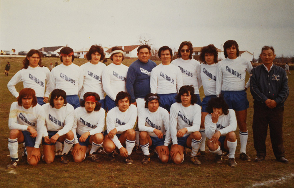 A soccer team poses for a photo. All the men except two are wearing white soccer jerseys, blue shorts, and white socks.